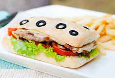 Ciabatta sandwich with grilled beef, tomatoes, cheese and lettuce with french fries Summer background stock photo