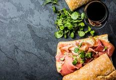 Ciabatta sandwich with jamon ham, arugula, red wine, slate background Royalty Free Stock Image