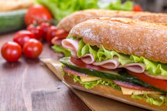 Ciabatta Sandwiches with ham. Ciabatta Sandwiches with lettuce, slices of fresh tomatoes, ham, turkey breast and cheese Royalty Free Stock Images
