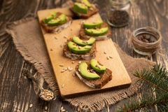 Ciabatta toasts, bruschetta with chopped avocado, olive oil, and seeds of sesame and sesame. Healthy vegetarian breakfast on stock photos