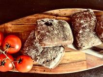 Ciabatta und Tomaten auf hölzerner Platte Lizenzfreies Stockbild