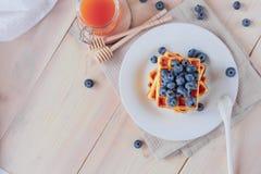 Cialde belghe con i mirtilli sulla tavola di legno leggera Prima colazione sana Immagini Stock