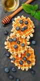 Cialde belghe con miele e le bacche fresche mirtillo e menta Fotografia Stock Libera da Diritti