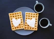 Cialde belghe deliziose con crema su un fondo nero e su due tazze di caffè Fotografie Stock Libere da Diritti