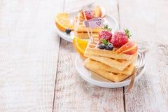 Cialde casalinghe con i frutti, lo sciroppo e lo zucchero su un piatto bianco su un fondo di legno Immagini Stock