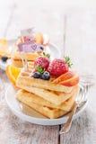 Cialde casalinghe con i frutti, lo sciroppo e lo zucchero su un piatto bianco su un fondo di legno Fotografie Stock