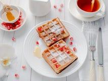 Cialde viennesi da acquolina in bocca deliziose con i semi del melograno e del miele su un piatto bianco, fondo di legno leggero Immagini Stock