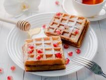 Cialde viennesi da acquolina in bocca deliziose con i semi del melograno e del miele su un piatto bianco, fondo di legno leggero Fotografie Stock Libere da Diritti