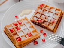 Cialde viennesi da acquolina in bocca deliziose con i semi del melograno e del miele su un piatto bianco, fondo di legno leggero Immagine Stock