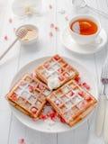 Cialde viennesi da acquolina in bocca deliziose con i semi del melograno e del miele su un piatto bianco, fondo di legno leggero Fotografia Stock