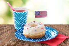 Ciambella con la decorazione della bandiera americana e del succo Fotografie Stock