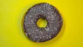 Ciambella deliziosa del cioccolato zuccherato che gira rapidamente su un piatto Vista superiore Fondo giallo stock footage