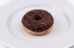 Ciambella dell'anello con la glassa del chololate sul piatto bianco Immagine Stock