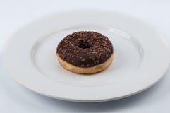 Ciambella dell'anello lustrata cioccolato sul piatto bianco Immagine Stock Libera da Diritti