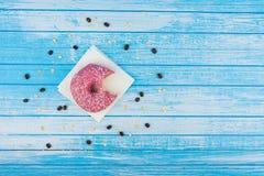 Ciambella dolce saporita pungente su carta sull'alta C bianca blu graffiata Immagini Stock