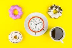 Ciambella fatta a casa con la tazza di caffè macchiato di caffè espresso e dell'orologio o Immagini Stock Libere da Diritti