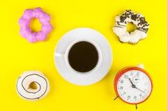 Ciambella fatta a casa con la tazza di caffè macchiato di caffè espresso e dell'orologio o Fotografia Stock