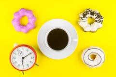 Ciambella fatta a casa con la tazza di caffè macchiato di caffè espresso e dell'orologio o Fotografia Stock Libera da Diritti