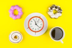 Ciambella fatta a casa con la tazza di caffè macchiato di caffè espresso e dell'orologio o Fotografie Stock Libere da Diritti