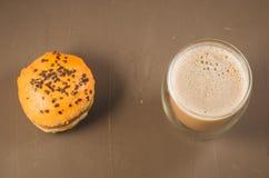 ciambella in glassa ed in un cappuccino /donut di vetro in glassa e un vetro del cappuccino su un fondo marrone Vista superiore fotografia stock libera da diritti