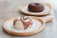 Ciambella lustrata con cioccolato sul vassoio di legno sulla tavola Fotografia Stock Libera da Diritti