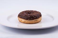 Ciambella lustrata del cioccolato sul piatto bianco Immagini Stock