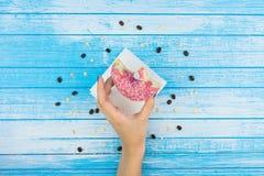 Ciambella rosa dolce saporita pungente tenuta della mano della donna su carta sull'SCR Immagini Stock Libere da Diritti