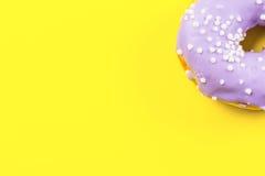 Ciambella rotonda porpora su fondo giallo Disposizione piana, vista superiore immagine stock libera da diritti