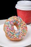 Ciambella variopinta in piatto e caffè bianchi con fondo nero Fotografia Stock Libera da Diritti