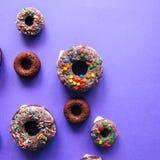 Ciambelle al forno del cioccolato con la glassa e la confetteria che completano o Fotografia Stock Libera da Diritti