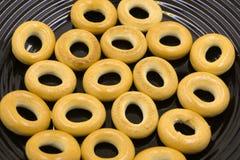 Ciambelle o ciambella sul nastro trasportatore in fabbrica, su un tipo di confetteria fritta della pasta o sull'alimento del dess fotografia stock