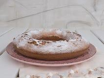 Ciambellone洒了与在桃红色陶瓷板材的搽粉的糖 免版税库存图片
