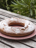 Ciambellone besprühte mit samtartigem Zucker auf der keramischen Platte, die mit rosa Baumwolle verziert wurde Platte, die auf Ho Lizenzfreies Stockfoto