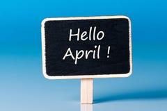 Ciao aprile - firmi, etichetta di legno con fondo blu primo giorno del mese di aprile Fotografie Stock
