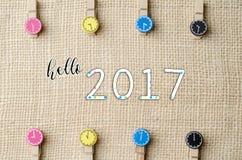 Ciao 2017 con le mollette da bucato di legno colourful sul fondo del sacco della tela da imballaggio Immagine Stock