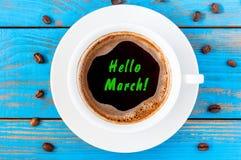 Ciao concetto di MARZO Mandi un sms a sulla tazza da caffè osservata superiore di mattina a fondo di legno blu La primavera comin Fotografia Stock Libera da Diritti