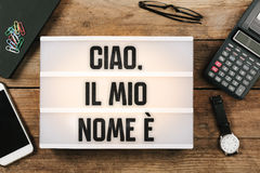 Ciao, il mio nome e, Italian text for Hello, My Name is. Vintage style light box on office desktop, high angle birds eye view royalty free stock photography