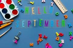 Ciao il testo di settembre sulla tavola dell'allievo o dell'insegnante con il lato delle offerte di scuola rasenta un fondo blu fotografia stock libera da diritti