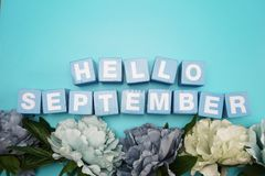 Ciao lettere di alfabeto di settembre con il mazzo del fiore su fondo blu immagini stock