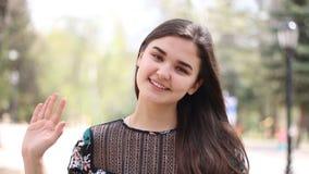 Ciao, ciao, ragazza 21 anno che ondeggia mano, benvenuto, ritratto della giovane donna nel parco video d archivio