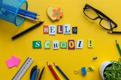 Ciao scuola Oggetti per la scuola su una tavola gialla Attrezzatura dell'allievo Di nuovo al concetto del banco Immagine Stock