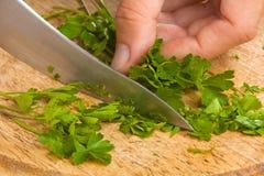 Ciapanie pietruszki liście na tnącej desce Zdjęcia Stock