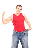 Ciężar straty mężczyzna daje kciukowi up i trzyma starą parę cajgi Fotografia Stock