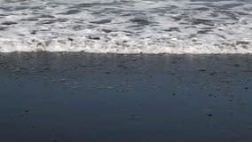 Ciasny strzał fala I piana Na Piaskowatej plaży zdjęcie wideo