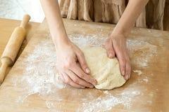 Ciasta drożdżowy lying on the beach na drewnianej tnącej desce kropiącej z mąką i kobiet rękami, obraz royalty free