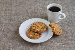 Ciastka na białym kubku z kawą i talerzu Tło burl Zdjęcia Stock