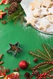 Ciastka odkurzali z sproszkowanym cukierem z Bożenarodzeniowymi dekoracjami na zieleni obrazy stock