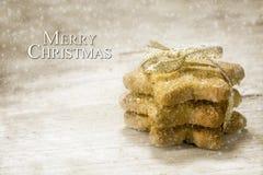 Ciastka w gwiazdowym kształcie z złotym faborkiem na nieociosanym drewnie, tex Obraz Stock