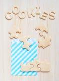 Ciastka w postaci łamigłówek i listy na stole Obrazy Royalty Free