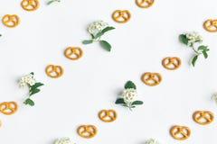 Ciastko kwiatów i precli wzór na białym tle Mieszkanie nieatutowy, odgórny widok Fotografia Stock